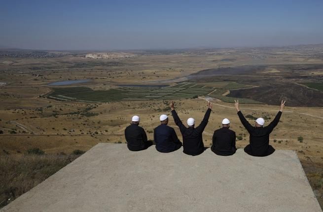 Druze men at the Israeli-annexed Golan Heights flash the V for victory sign as they look out across the southwestern Syrian province of Quneitra, visible across the border (AFP)
