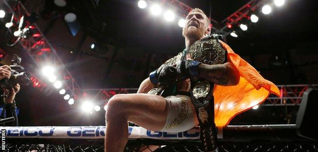 Conor McGregor celebrates with his two championship belts after defeating Eddie Alvarez