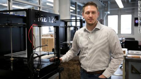 Zac DiVencenzo, COO of Juggerbot 3D, stands next to a 3D printer.