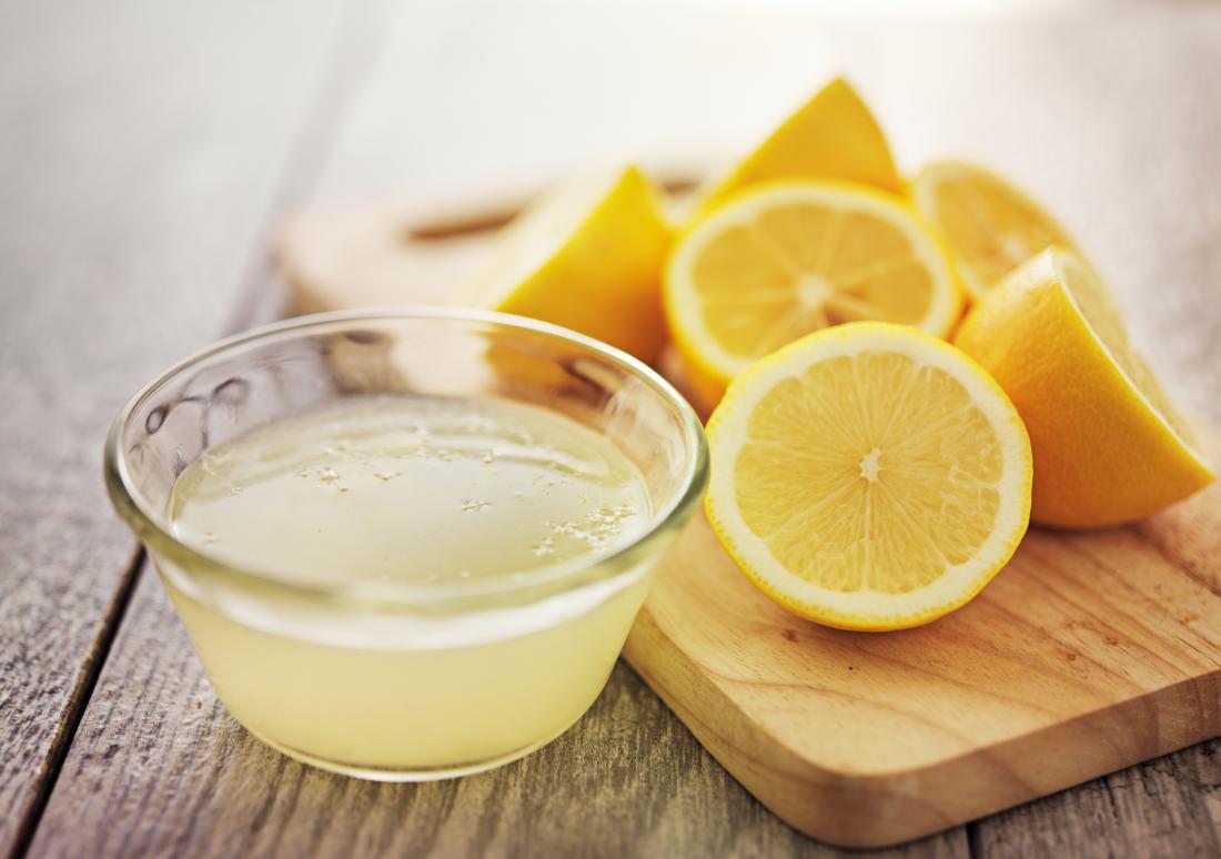 Cut up lemons on chopping board with bowl of lemon juice