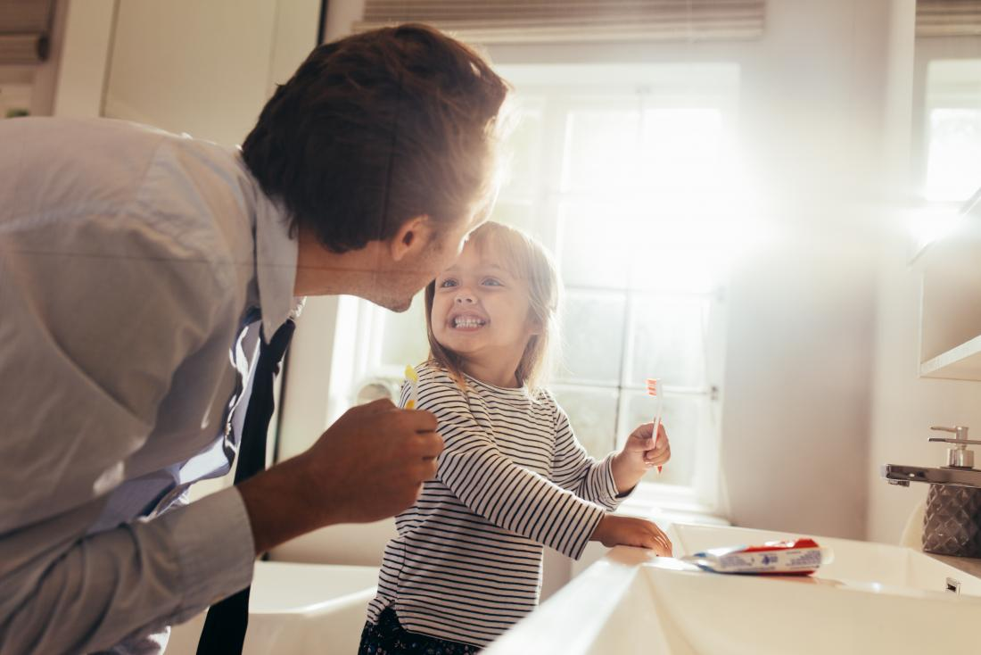 Father teaching child to brush teeth