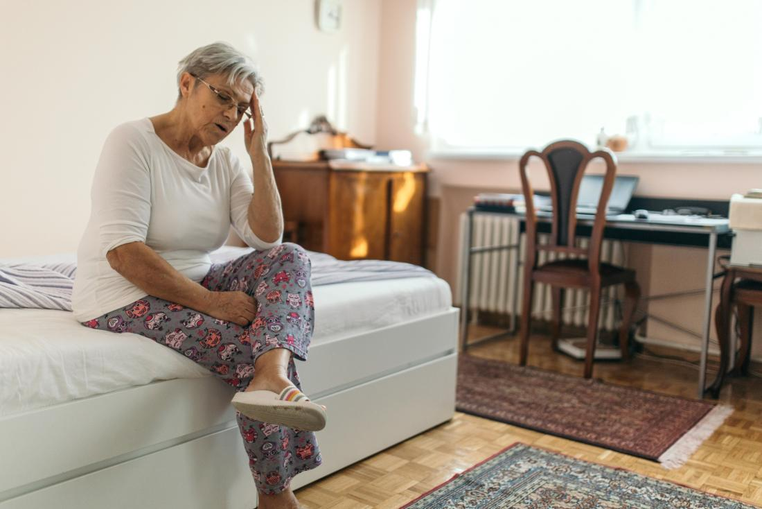 older woman sitting on the edge of a bed
