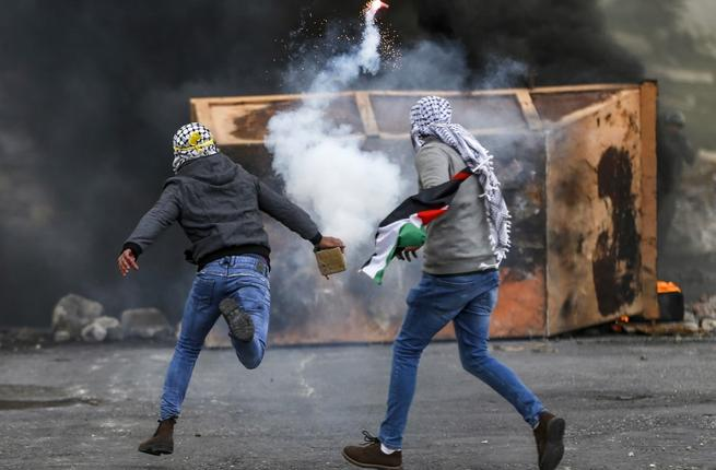 A Palestinian man throws back a tear gas canister during clashes with Israeli forces following a demonstration marking