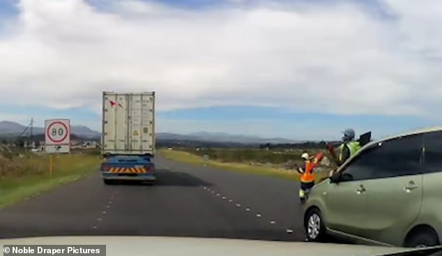 Two workers wearing hi-viz jackets in the middle of the road are ignored by an overtaking car near Cape Town