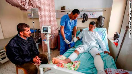 Al-Badan (right) receives treatment at Beit Jala Hospital near Bethlehem, as his father (left) looks on.