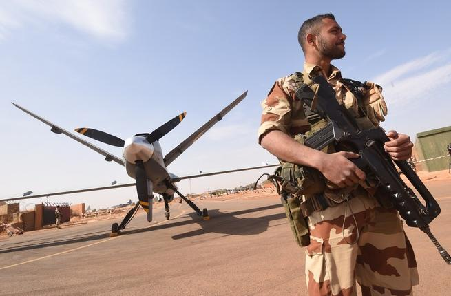 A French soldier of the aerial detachment of the Operation Barkhane stands guard near a Reaper drone at the Nigerian military airport Diori Hamani in Niamey. (AFP)