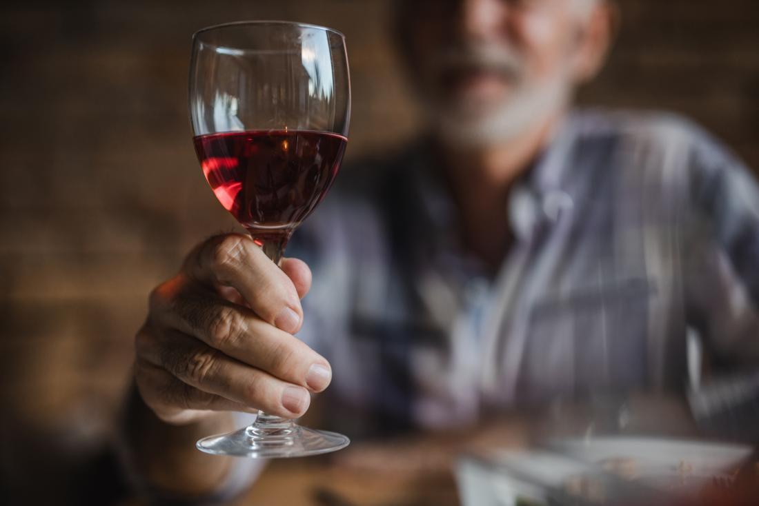 man holding glass of wine