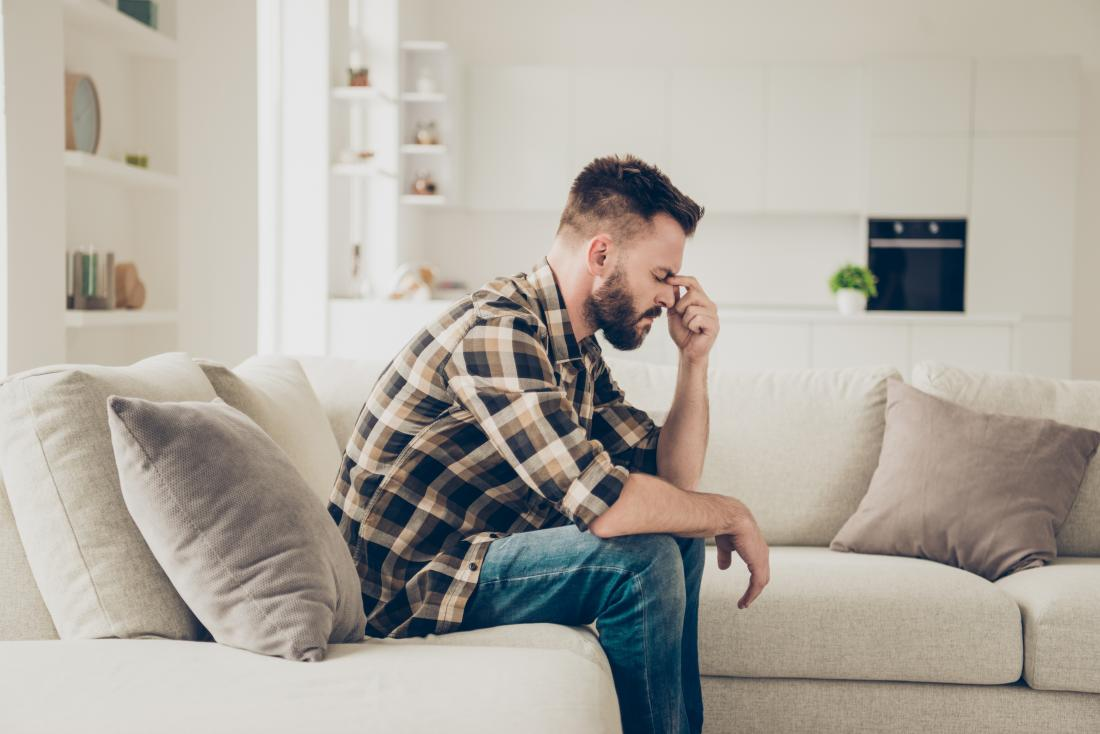 man with headache sitting on sofa