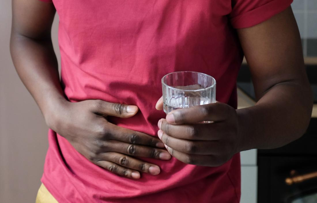 Man with stress ulcer holding stomach in pain along with glass of water