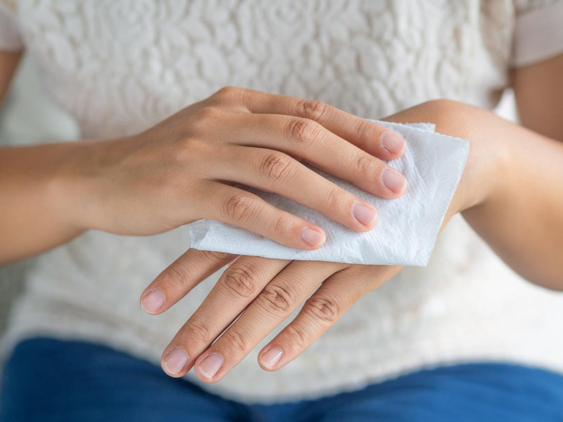 woman applying warm wet compress to skin on back of hand