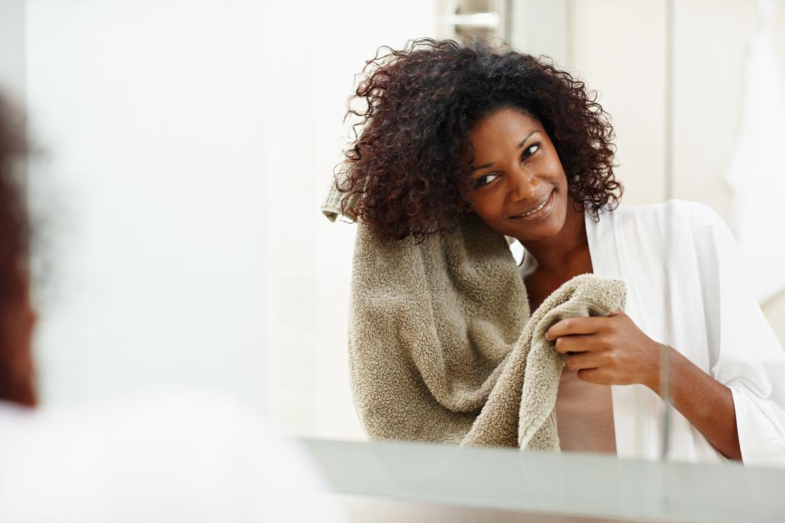 Woman washing and drying hair in bathroom