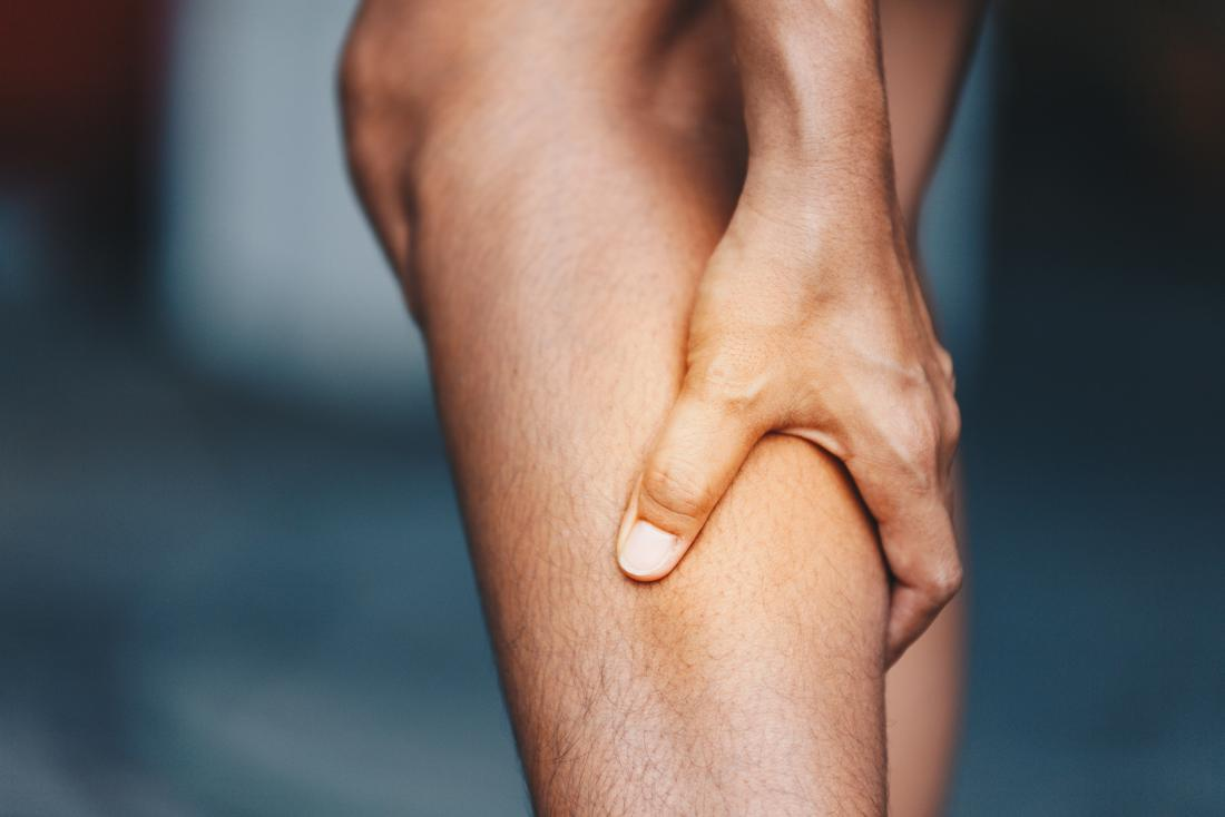 A person holding their leg in pain due to diabetes leg pain