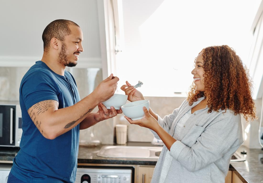Couple eating breakfast cereal from bowls in kitchen.