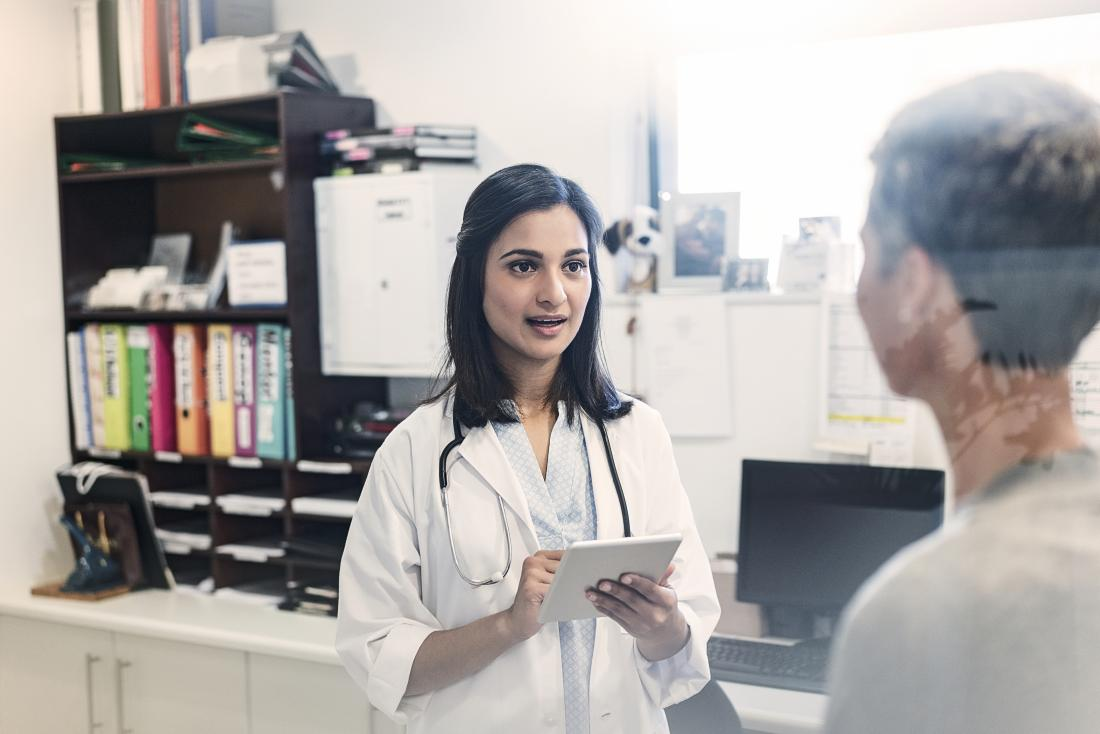 Doctor with patient in office discussing pap smear test