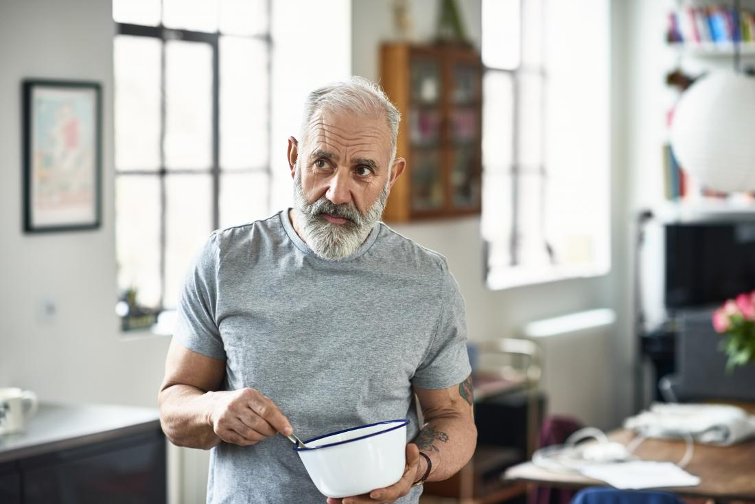 Mature or senior man in house mixing food in bowl