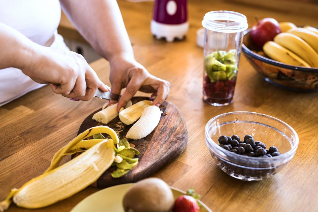 Person chopping or cutting fruits for smoothie or juice, including banana, kiwi, and blueberries