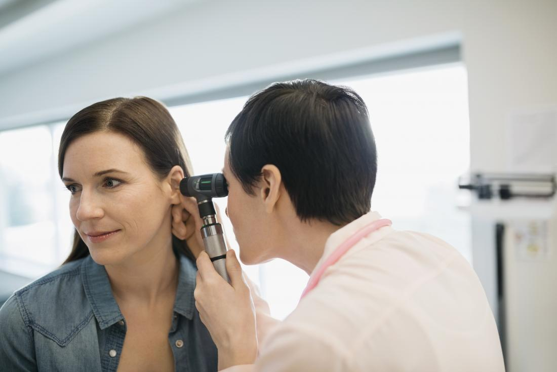 woman having ear examined by doctor with otoscope
