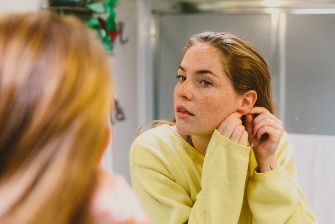 Woman with ear piercings looking in bathroom mirror touching behind ear.