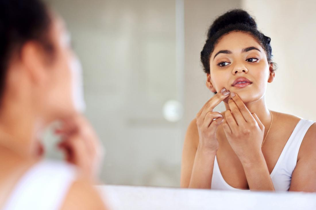 woman examining the skin on her face in the mirror