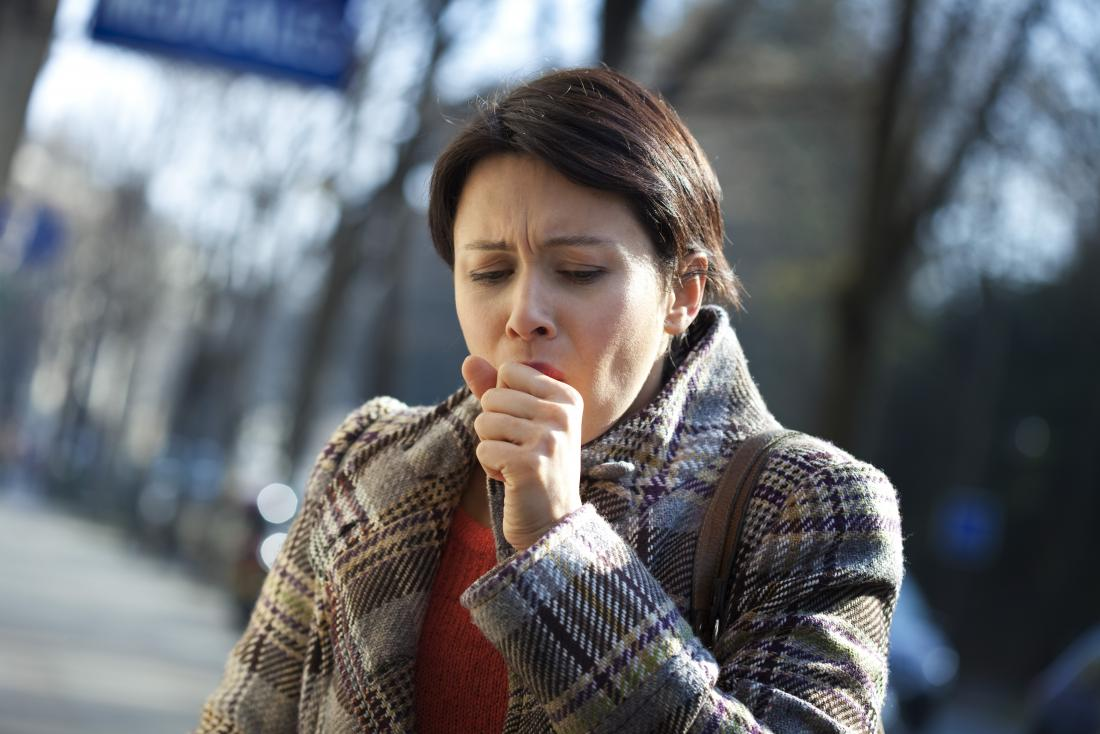 Woman with brittle asthma coughing into hand