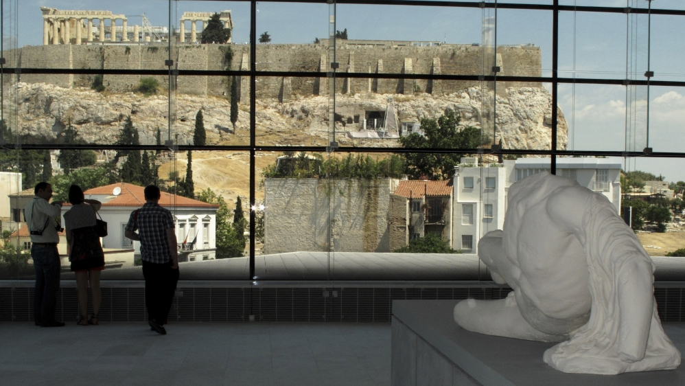 Visitors look at the temple of the Parthenon from inside the new Acropolis museum in Athens